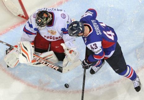 Томас Суровый (Словакия) пытается забить шайбу на воротах с вратарём Ильёй Брызгаловым на встрече России и Словакии в матче отборочного тура ЧМ по хоккею. Фото: ALEXANDER NEMENOV/AFP/Getty Images