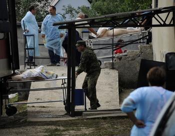 Тела погибших от наводнения погружают на грузовик в Крымске 8 июля 2012. Фото: MIKHAIL MORDASOV/AFP/GettyImages)