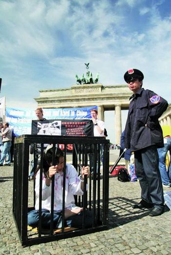 Воспроизведение пыток: на этой фотографии воспроизводится сцена пыток, которым подвергаются последователи духовной практики Фалуньгун в Китае. Эта сцена пыток была показана в Берлине, недалеко от Бранденбургских ворот, в мае 2007 года. Фото с сайта theepochtimes.com