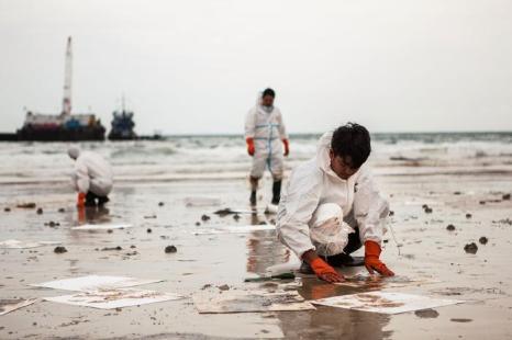 Около 700 волонтёров и специалистов задействованы в очищении пляжей бухты Прао Бэй от нефти в пятницу, 2 августа 2013 года. Фото: Nicolas Axelrod/Getty Images