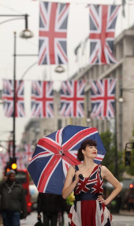 Модельер и модель Жасмин Гиннесс (Jasmine Guinness) представляет флаги на улице Оксфорд-стрит в честь предстоящего брильянтового юбилея королевы Елизаветы II в Англии. Фоторепортаж. Фото: Oli Scarff/Getty Images