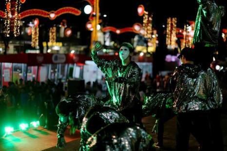 Исполнители танцуют перед людьми во время шоу рождественских развлечений на Орчард Роад. Фото: Chris McGrath / Getty Images