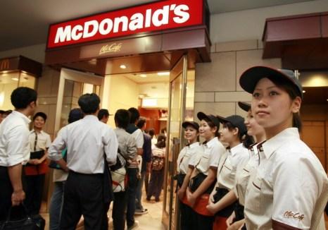 Официанты «Макдоналдса» встречают клиентов у входа в кафе. Япония. Фото: YOSHIKAZU TSUNO/AFP/Getty Images