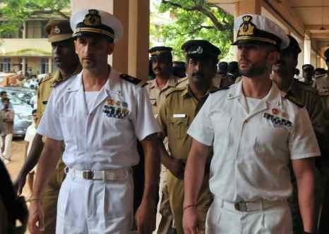 Итальянских морских пехотинцев Массимилиано Латорре и Сальваторе Джироне сопровождают индийские полицейские. Фото: STRDEL/AFP/GettyImages