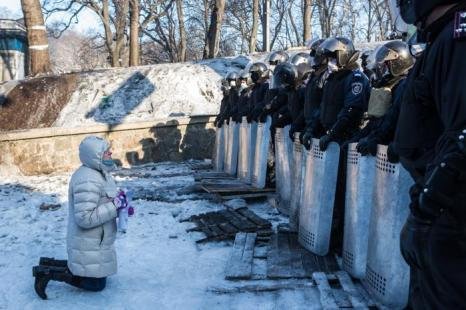 Женщина стоит на коленях перед линией полицейских в центре Киева 24 января 2014 года. Фото: Brendan Hoffman/Getty Images