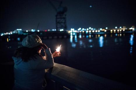 Молодая девушка участвует в минуте молчания на побережье Нью-Йорка в первую годовщину урагана «Сэнди», почтив память более 150 погибших. Фото: Andrew Burton / Getty Images