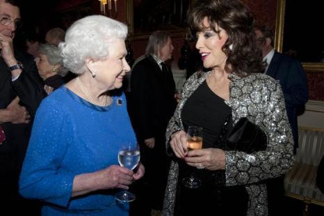Королева Великобритании Елизавета II беседует с актрисой Джоан Коллинз на приёме в Букингемском дворце  17 февраля 2014 года. Фото: David Crump - WPA Pool/Getty Images