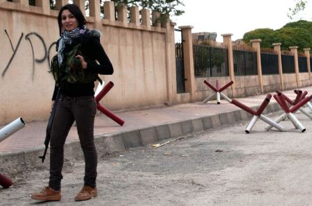 (FILES) A picture taken on November 12, 2012, shows a Kurdish woman and member of the Popular Protection Units (YPG), an armed opposition group fighting against the Syrian government in Syrian Kurdistan, standing with her gun as she patrols a street outside the former Syrian Political Force's building which was abandoned peacefully by Syrian forces loyal to President Bashar al-Assad, in the northern Syrian border village of Deriko Hamko. Some 150 Kurdish women in the north Syrian province of Aleppo set up a fighting battalion, a monitoring group said on February 23, 2013, days after Kurdish militia and the rebel Free Syrian Army agreed to stop fighting.  AFP PHOTO/GIULIO PETROCCO        (Photo credit should read guilio petrocco/AFP/Getty Images)