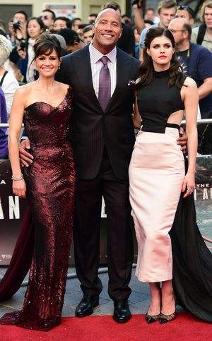 (L to R) US actress Carla Gugino, Actor Dwayne 'The Rock' Johnson, US actress Alexandra Daddario pose on the carpet as they arrive to attend the World premiere of the film 'San Andreas' in London on May 21, 2015. AFP PHOTO / LEON NEAL        (Photo credit should read LEON NEAL/AFP/Getty Images)