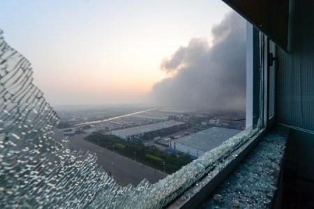 Из разбитого окна квартиры виден дым на месте взрывов в Тяньцзине, Китай, 13 августа 2015 года. Фото: STR/AFP/Getty Images