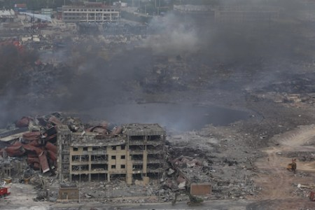 CORRECTION Smoke rises at the site of an explosion in Tianjin on August 14, 2015.  Chinese authorities struggled to extinguish fires and identify dangerous chemicals at a devastated industrial site, two days after giant explosions killed dozens and left residents in fear of being cloaked in a toxic cloud.    CHINA OUT AFP PHOTO        (Photo credit should read STR/AFP/Getty Images)