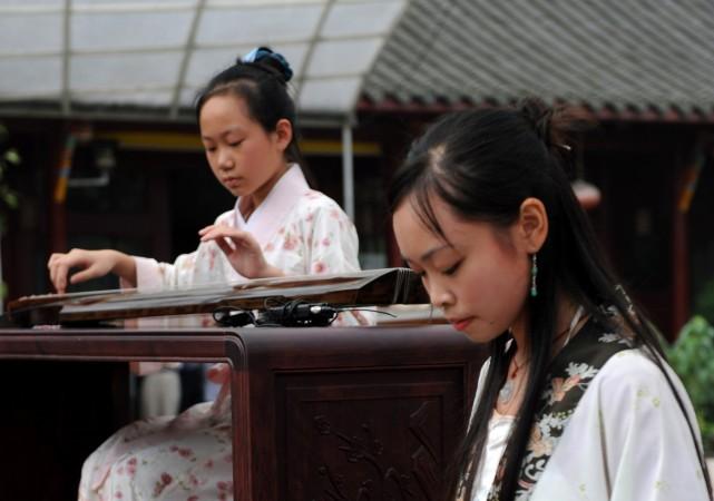 древний Китая, молодые китаянки играют на гуцине ― традиционном китайском инструменте.