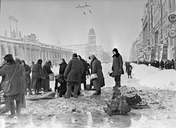 Жители блокадного Ленинграда набирают воду, появившуюся после артобстрела в пробоинах в асфальте. Фото: Boris Kudoyarov/wikipedia.org/CC BY-SA 3.0