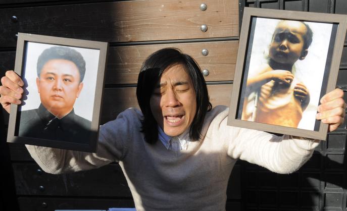 Мужчина держит в одной руке фотографию северокорейского лидера Ким Чен Ына, а в другой - фотографию ребёнка, умершего от недоедания. Фото: PARK JI-HWAN/AFP/Getty Images