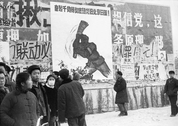 """BEIJING, CHINA - JANUARY21: A small group of Chinese youths walk past several dazibaos, the revolutionary placards, in February 1967 in downtown Beijing, during the """"Great Proletarian Cultural Revolution"""". Since the the cultural revolution was launched in May 1966 at Beijing University, Mao's aim was to recapture power after the failer of the """"Great Leap Forward"""". (Photo credit should read JEAN VINCENT/AFP/Getty Images)"""