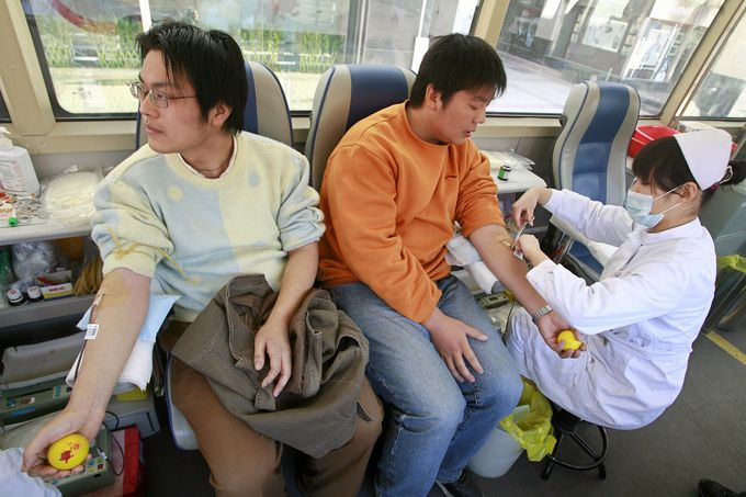 Two Chinese men donate blood at a mobile bloodbank bus in Beijing, 17 November 2007. Young Beijing residents are bucking tradition and stepping forward to answer the latest call to duty by city officials -- to donate blood for next year's Olympics as Chinese blood donors did not exists 10 years ago, according to a contemporary US embassy report, and hospitals had to rely on a high-risk market in blood that was bought and sold with little medical supervison. AFP PHOTO/TEH ENG KOON (Photo credit should read TEH ENG KOON/AFP/Getty Images)