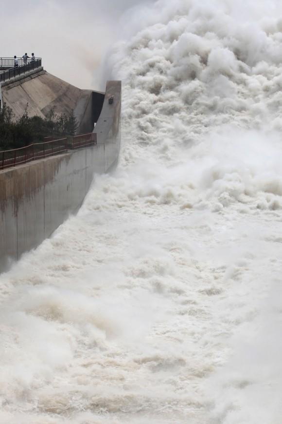 Люди наблюдают, как бурлят воды на дамбе на реке Хуанхэ. 23 июля 2013 г. Фото: STR/AFP/Getty Images