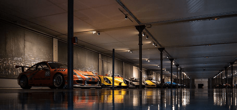 A modern garage with a neatly done epoxy floor and lots of luxury cars.