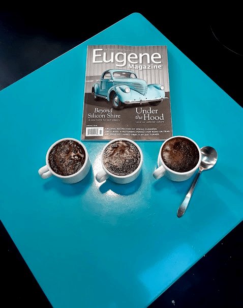Cupped Coffee in front of Eugene magazine on a blue table.