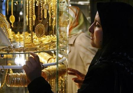 A Palestinian woman looks at gold jewellery at the traditional gold market, were people buy as well ..