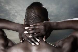 Male model Gavin hands in neck - back view
