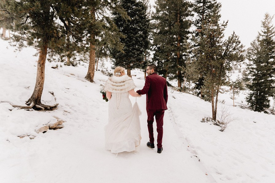 Couple walks through path from snowy Sapphire Point elopement