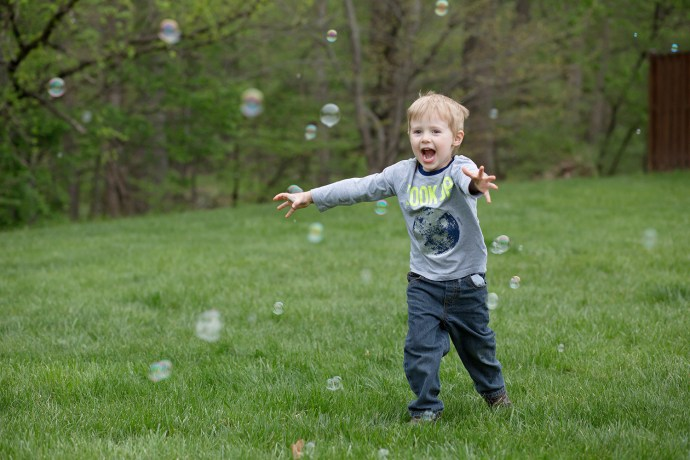 boy smiling and running through bubbles