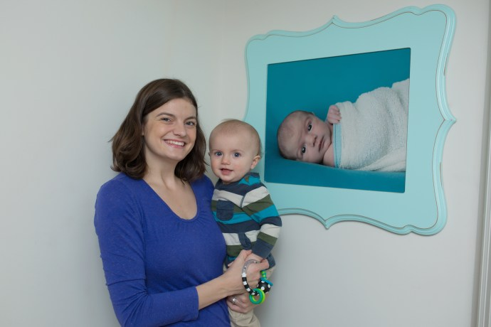 mom and baby next to wall art of baby