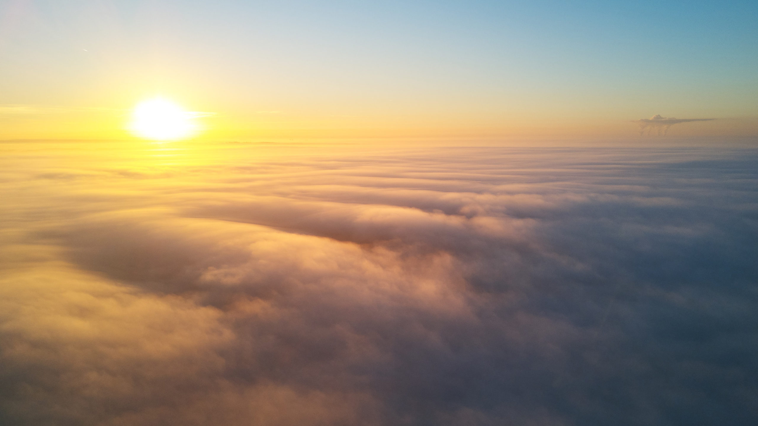 View of the sun rising above the clouds