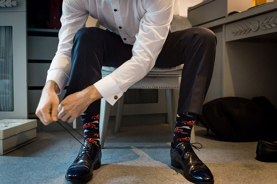 groom wearing colourful socks tying his shoes