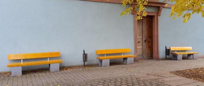 Sitzbänke rund um die Kirche erhalten ihre Rückenlehnen