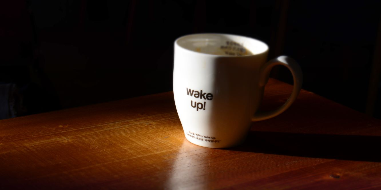 "Coffee mug with the words ""wake up!"" written on them."