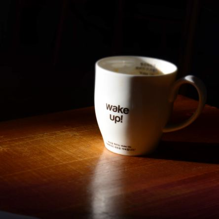 """Coffee mug with the words """"wake up!"""" written on them."""