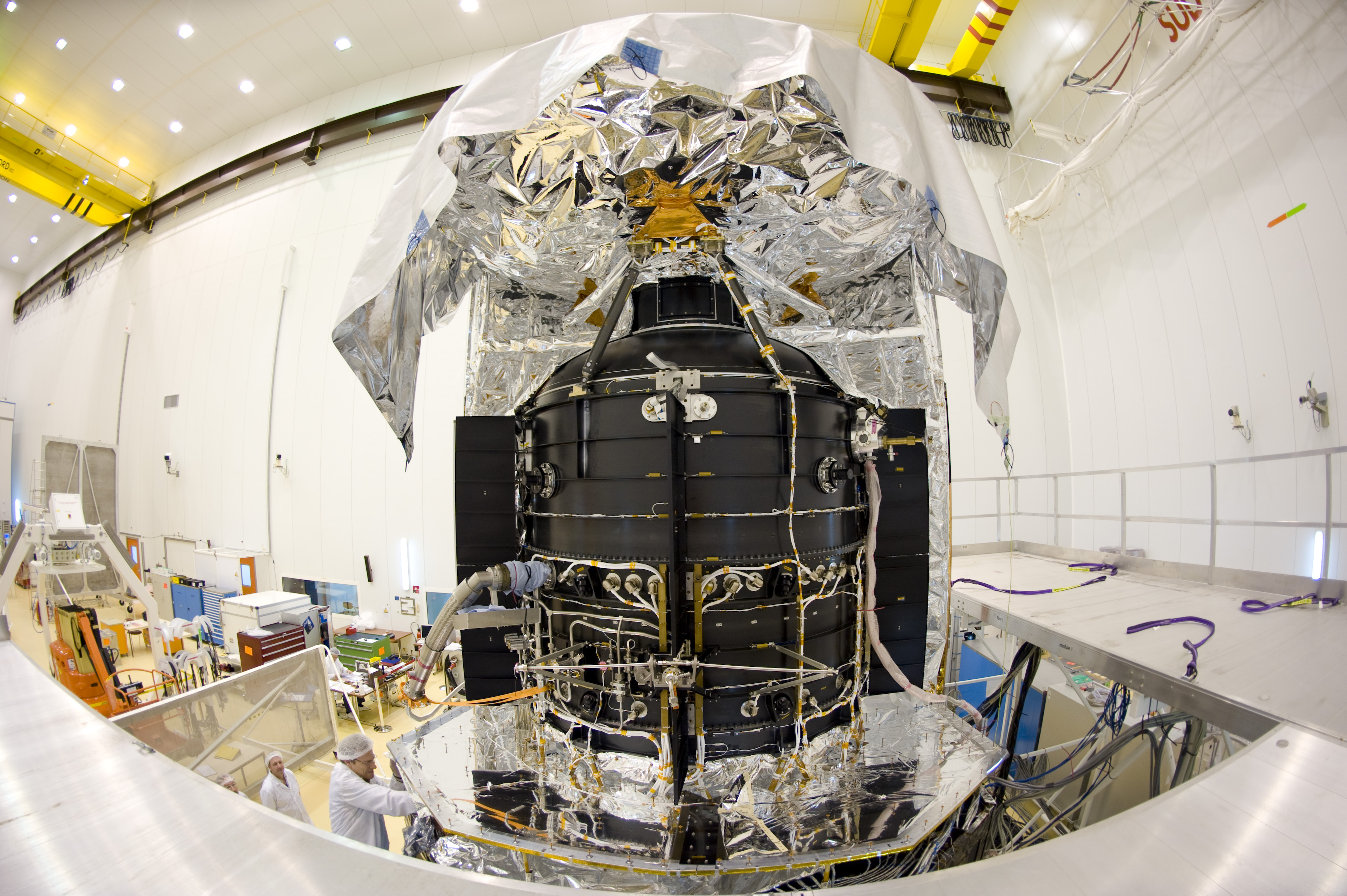 The Herschel spacecraft in the S1B clean room at Europe's launch site (CSG) in Kourou, French Guiana. A protective foil is draped over the satellite to protect Herschel's giant primary mirror from contamination.
