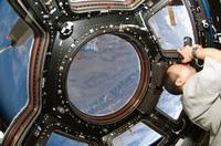 Soichi Noguchi utiliza una cámara de fotos en una ventana en la cúpula