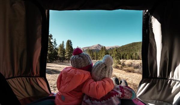 Two girls hugging from inside campervan