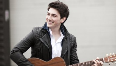 Brendan Murray is holding a guitar standing outside a building.