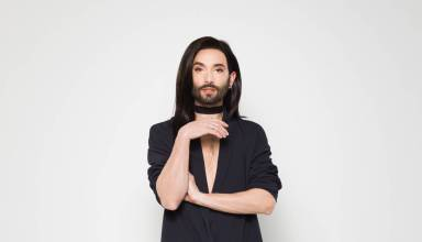 Conchita Wurst stands against a grey wall.
