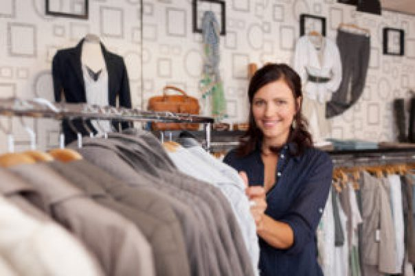 Smiling Woman Choosing Shirt In Clothing Store