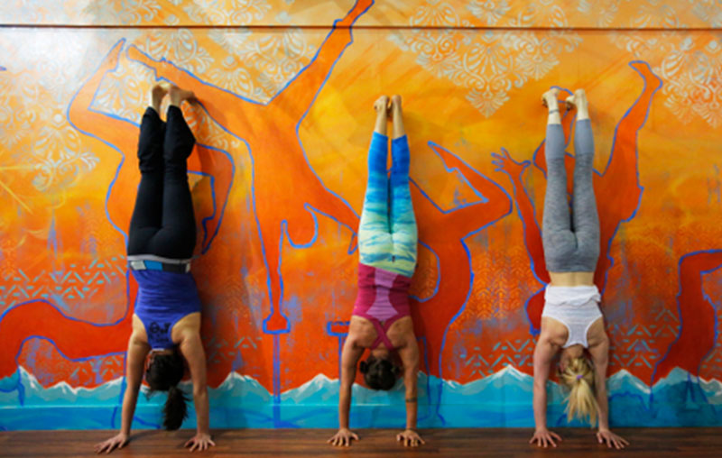students in a handstand against a wall