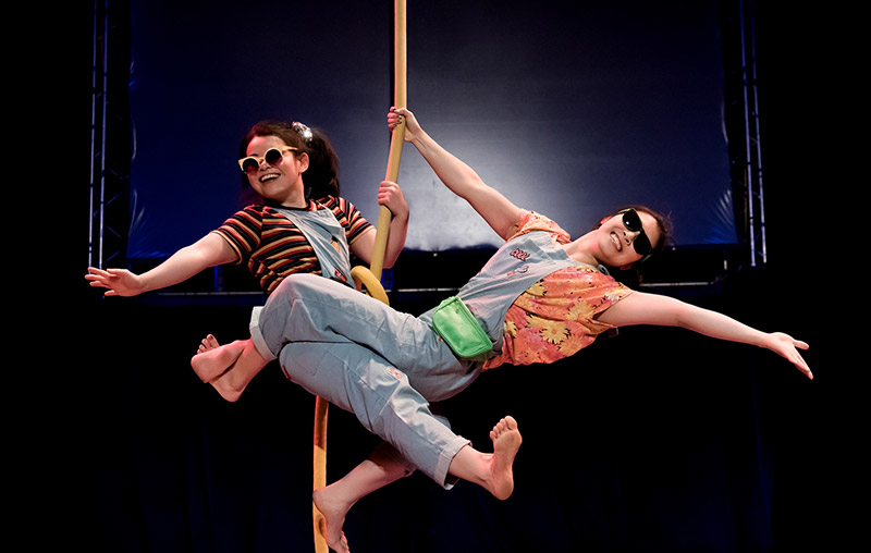 two performers smiling on an aerial rope