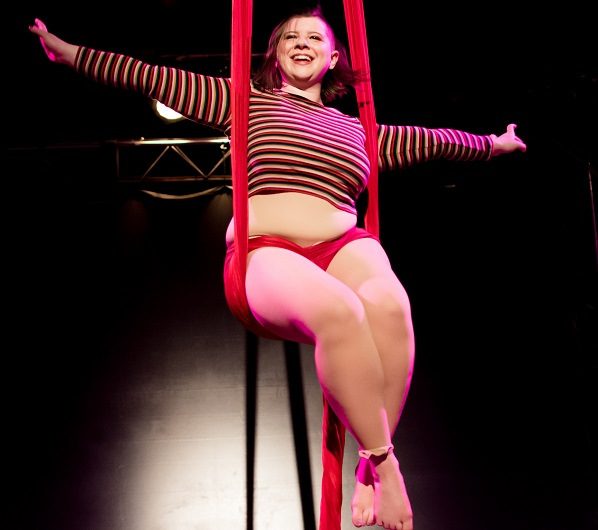 smiling woman in sitting position on aerial silks