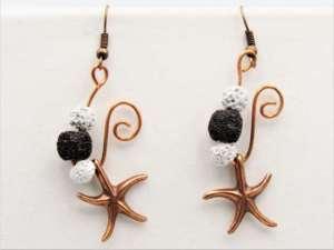 Χειροποίητα Σκουλαρίκια μπρονζέ αστερίες με άσπρες και μαύρες ηφαιστειακές πέτρες.