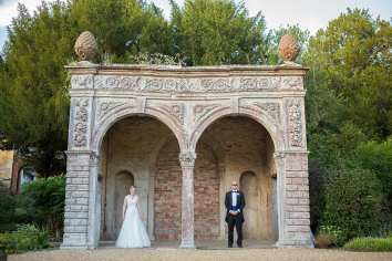bride and groom stand under the orangery