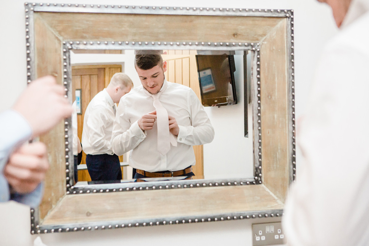 groom fixing his tie on wedding morning in mirror at mythe barn