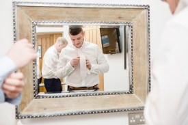 groom fixing his tie on wedding morning in mirror at mythe barn