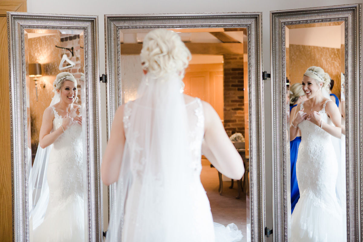 bride looking in mirror before ceremony at mythe barn