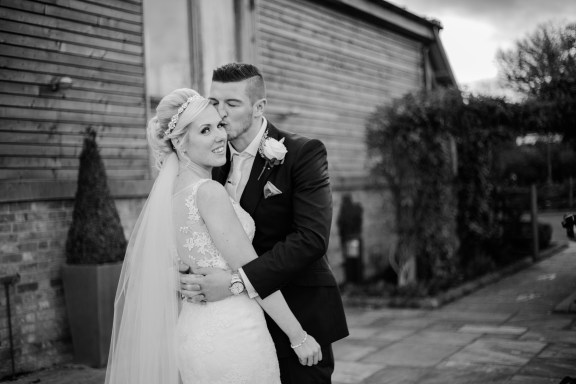 groom kissing bride in garden at Winter Wedding Mythe Barn Warwickshire