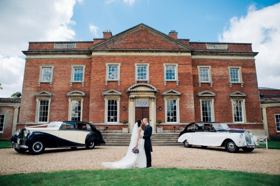 Bride and Groom Kiss infront of Wedding Cars at Kelmarsh Hall