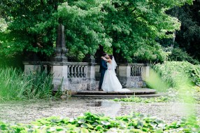 Bride and groom Kiss next to pond dunchurch park